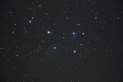 Die Plejaden sind ein sehr ausgedehnter Sternhaufen, um den das schwache Schimmern eines Reflexionsnebels erahnbar ist.